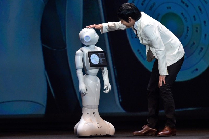 CHIBA, JAPAN - JUNE 18: Comedian Koji Imada talks with Pepper during the news conference on June 18, 2015 in Chiba, Japan. Softbank Corp. announced that its humanoid product, Pepper, developed by the company's Aldebaran Robotics unit, will be available for consumers at 198,000 yen on June 20, 2015. SoftBank Corp. also announced that Alibaba Group Holding Limited and Foxconn Technology Group reached an agreement that Alibaba and Foxconn will each invest 14.5 billion in SoftBank Robotics Holdings Corp., to promote Softbank's robotic business including Pepper to the global market. (Photo by Koki Nagahama/Getty Images)